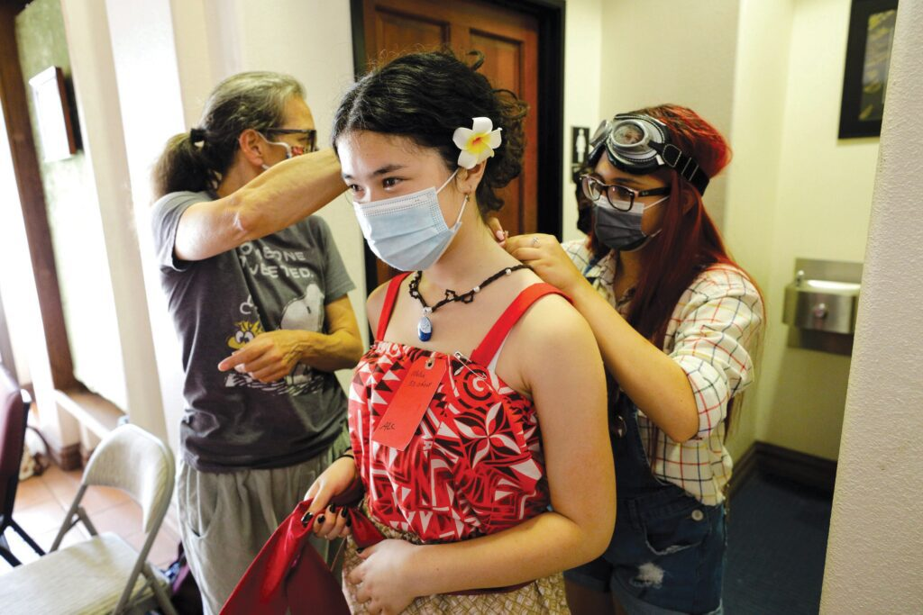 """TEAM EFFORT—Costumer Mary Abraham, left, and junior counselor Sierra Armstrong, 16, help Melia Moss, 14, with a dress for her character, Moana, on July 15 during High Street Arts Center's Summer Youth Camp in Moorpark. The camp is staging the musical """"Moana Jr."""" MICHAEL COONS/Acorn Newspapers"""